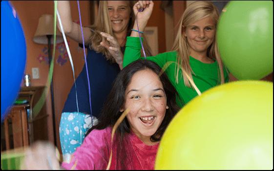 Tre piger, der fejrer og griner med balloner.